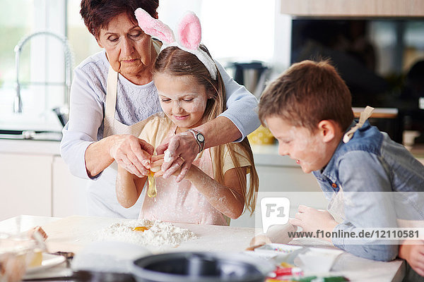 Großmutter hilft Mädchen beim Osterbacken an der Küchentheke