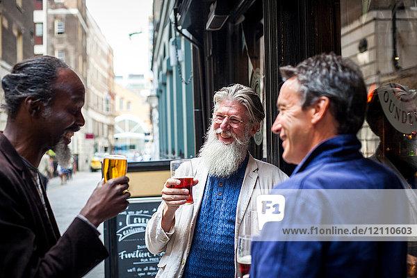 Drei reife Männer  die vor der Kneipe stehen  Biergläser halten und lachen