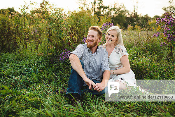 Couple sitting in tall grass looking away smiling