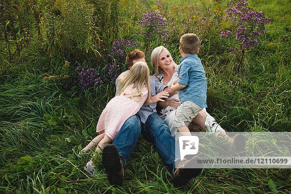 Eltern und Kinder liegen gemeinsam im hohen Gras
