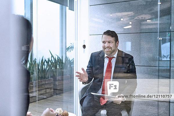 Blick durch die Glaswand von Kollegen  die sich im Büro treffen