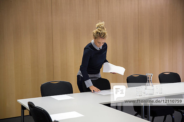 Woman laying out paperwork in conference room