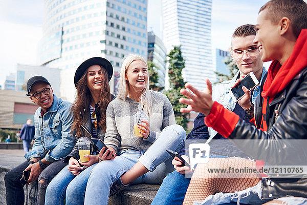 Fünf junge erwachsene Freunde sitzen auf einer Mauer und unterhalten sich in der Stadt