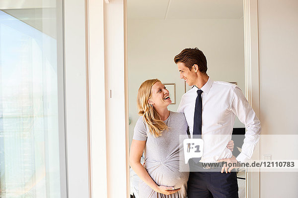 Happy pregnant couple gazing at each other in living room