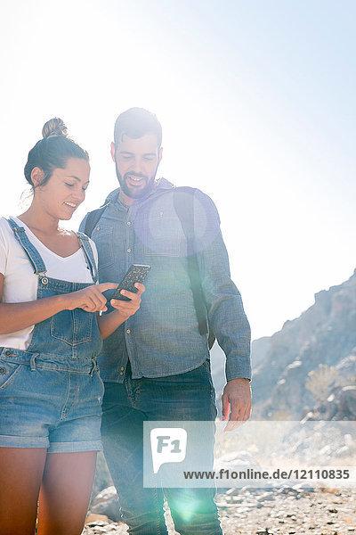 Junges Wanderpaar betrachtet Smartphone im sonnenbeschienenen Tal  Las Palmas  Kanarische Inseln  Spanien