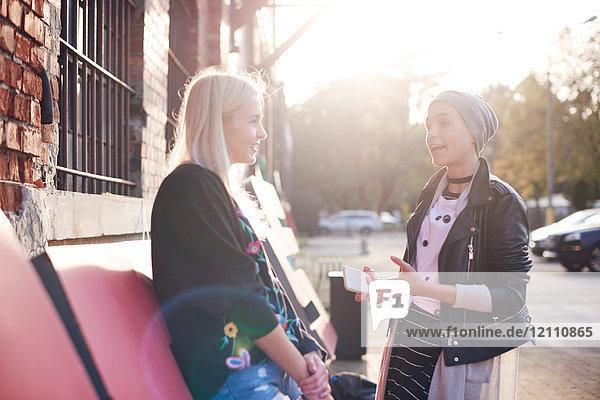 Zwei junge Freundinnen unterhalten sich auf der sonnenbeschienenen Straße der Stadt