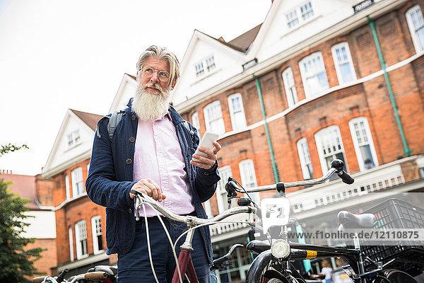 Erwachsener Mann steht neben dem Fahrrad und hält ein Smartphone