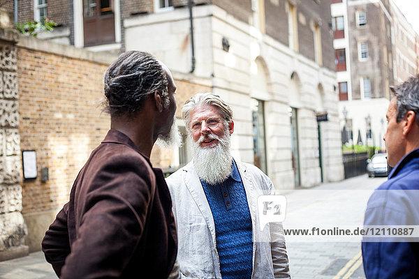 Drei reife Männer im Freien  die sich unterhalten