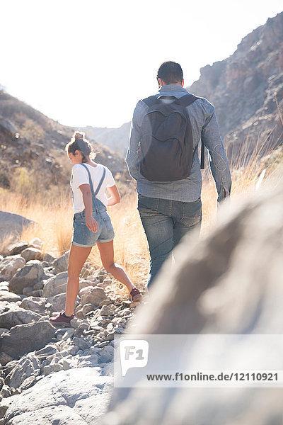 Rückansicht eines jungen Wanderpaares beim Wandern über Felsen im Tal  Las Palmas  Kanarische Inseln  Spanien