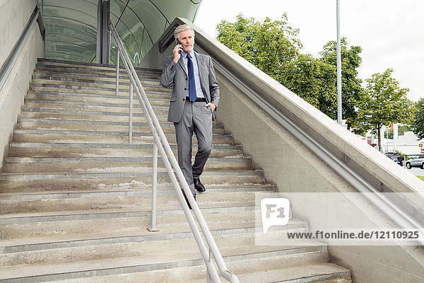 Businessman walking down steps making telephone call on smartphone