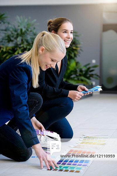 Zwei junge Geschäftsfrauen kauern auf der Büroetage und betrachten Farbmuster