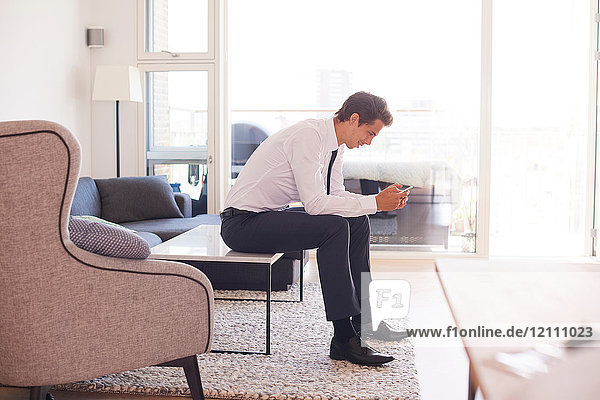Businessman sitting on coffee table looking at smartphone