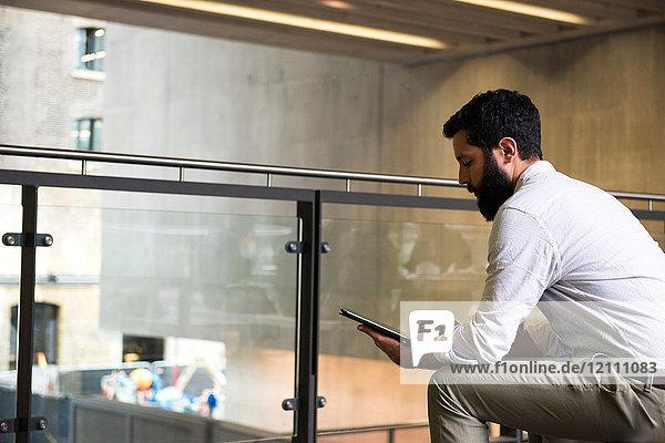 Mann im Zwischengeschoss eines Bürogebäudes mit digitalem Tablet