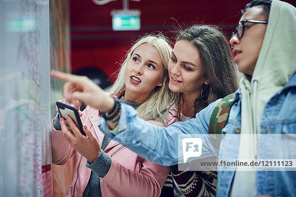 Drei junge erwachsene Freunde zeigen in der U-Bahn-Station auf eine Karte