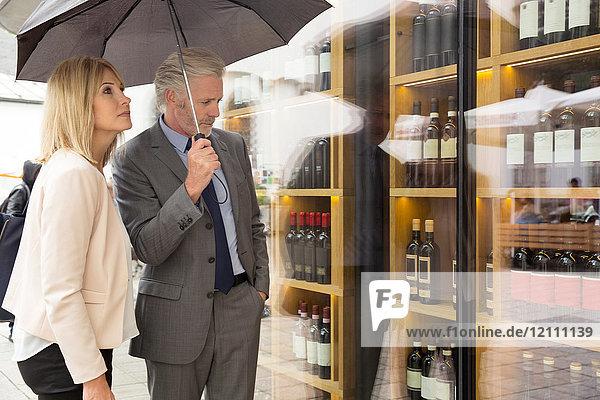 Couple window shopping in wine shop window