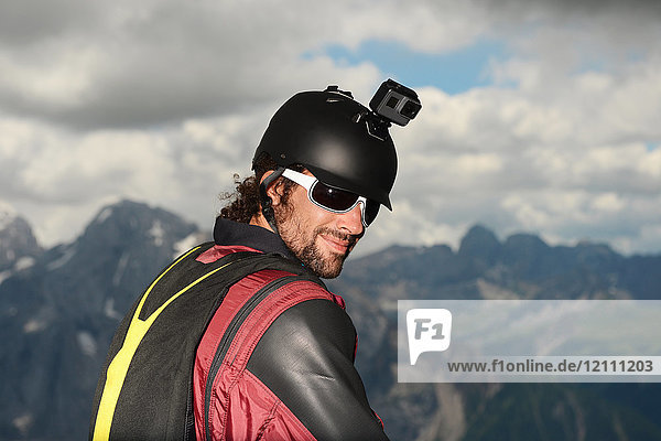 Portrait of base jumper wearing wingsuit with action camera on helmet  Dolomite mountains  Canazei  Trentino Alto Adige  Italy  Europe