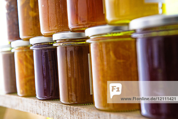 Jars of different flavored jams on a shelf