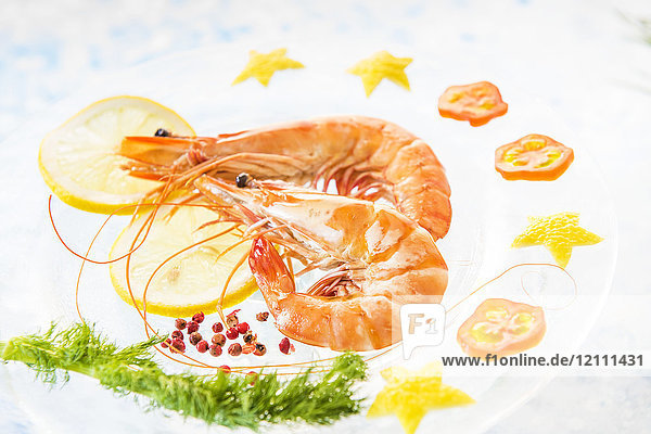 Plate of king prawns with lemon and pink peppercorns