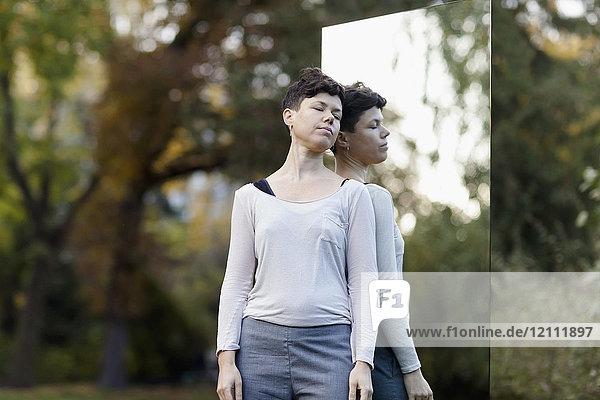 Frau mit geschlossenen Augen  die sich am Spiegel gegen Bäume im Park lehnt.