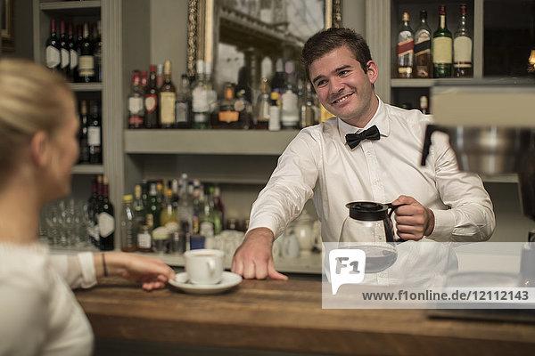 Lächelnder Barkeeper bei der Zubereitung einer Tasse Kaffee für die Frau