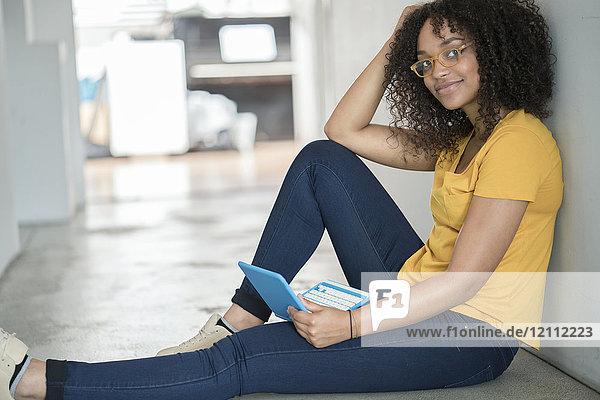 Junge Frau sitzt auf dem Boden mit Laptop