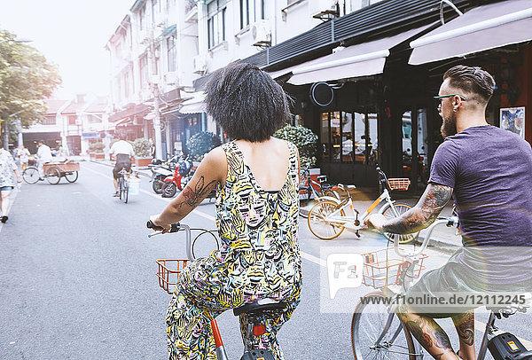Multi-ethnisches Hipster-Paar radelt entlang der Stadtstraße,  Shanghai Französische Konzession,  Shanghai,  China