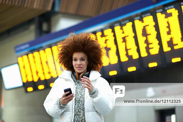 Junge Frau am Bahnhof mit Smartphone in der Hand