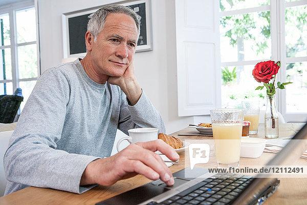 Mann benutzt Laptop während des Frühstücks