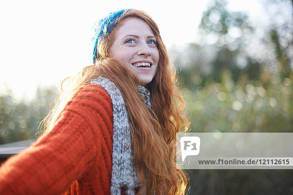 Portrait of red haired woman looking up smiling