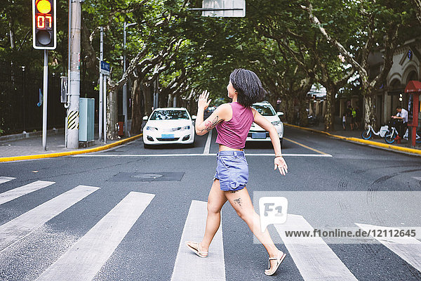 Woman marching across pedestrian crossing  Shanghai French Concession  Shanghai  China