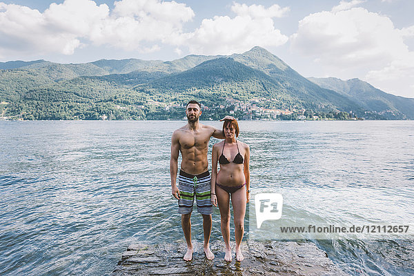 Portrait of couple in swimwear standing on water's edge Lake Como  Lombardy  Italy