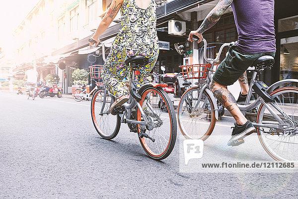 Taillenansicht eines multiethnischen Hipster-Paares  das mit dem Fahrrad die Straße entlang fährt  Schanghai Französische Konzession  Schanghai  China