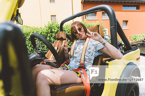 Portrait of young woman on road trip in off road vehicle giving peace sign  Como  Lombardy  Italy