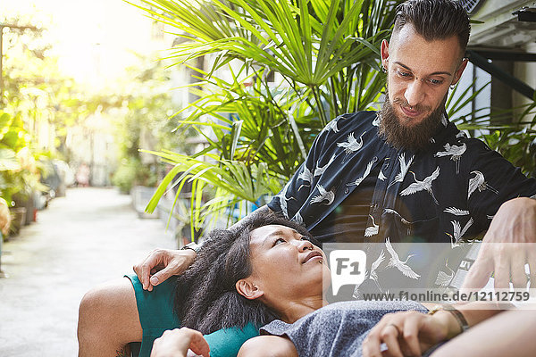 Multiethnisches Paar  das auf einer Gartenbank in einer Wohngasse liegt  Shanghai Französische Konzession  Shanghai  China