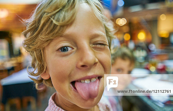 Portrait of boy looking at camera  poking out tongue