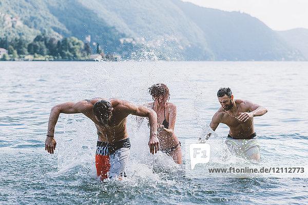 Drei junge erwachsene Freunde spielen im Comer See  Como  Lombardei  Italien