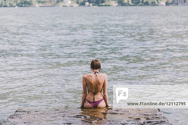 Rear view of young woman in bikini looking out at Lake Como  Lombardy  Italy