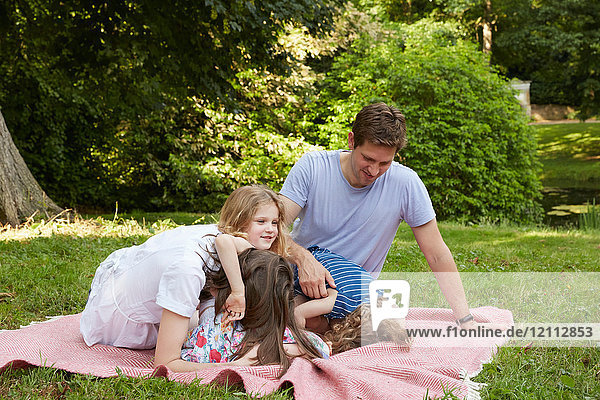 Mid adult parents with two daughters bending forward on picnic blanket in park