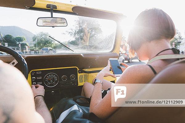Junge Frau betrachtet Smartphone im Geländewagen  Como  Lombardei  Italien