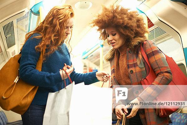 Zwei junge Frauen im Zug  die in Einkaufstaschen schauen