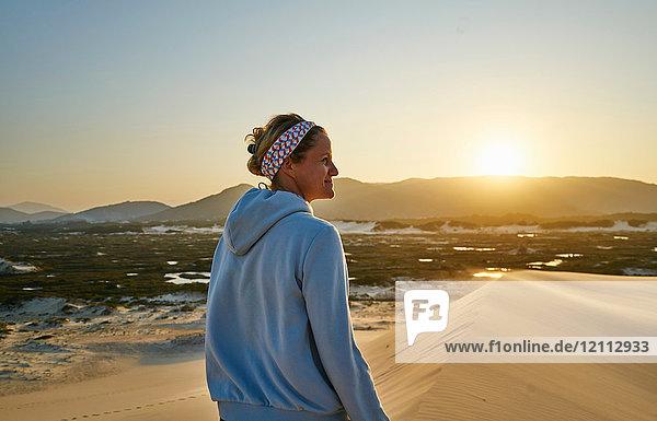 Frau schaut weg beim Sonnenuntergang über den Dünen  Florianopolis  Santa Catarina  Brasilien  Südamerika