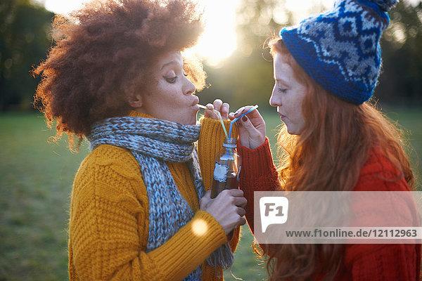 Zwei junge Frauen in ländlicher Umgebung  die aus einer Flasche mit Strohhalmen trinken