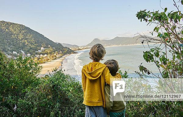 Jungen auf einer Klippe  die zum Strand wegschauen  Florianopolis  Santa Catarina  Brasilien  Südamerika
