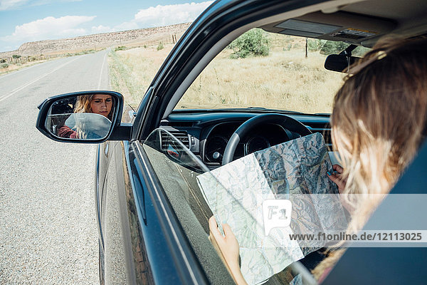 View over shoulder of woman sitting in car looking at map