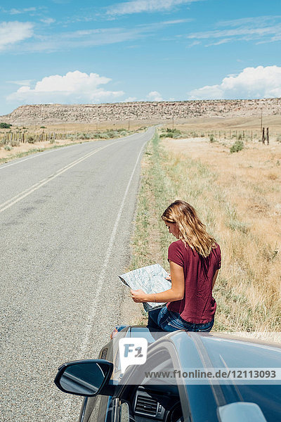 Woman sitting on car looking at map