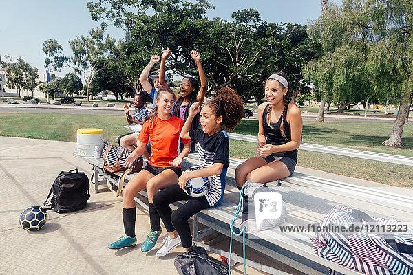 Männlicher Lehrer und Schülerinnen beim Fußballtraining auf dem Schulsportplatz