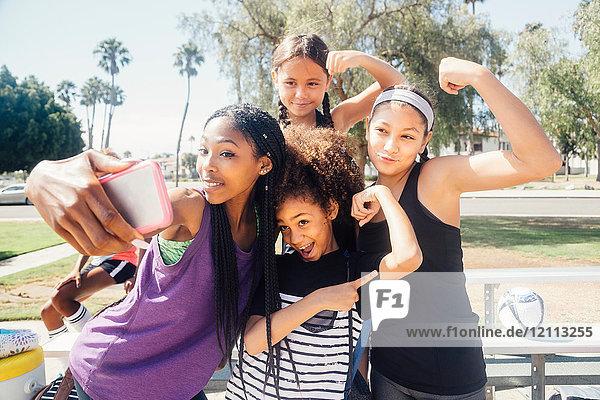 Schülerinnen-Fussballspielerinnen mit Smartphone-Selfie auf dem Schulsportplatz
