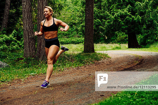 Young female weightlifter running through forest