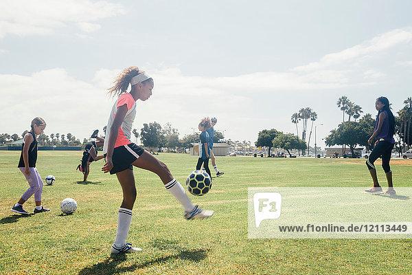 Schulmädchen üben auf dem Schulsportplatz mit dem Fussball