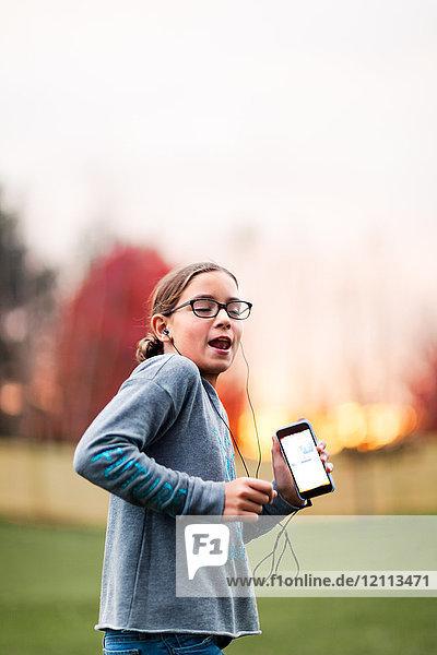 Mädchen hört über Smartphone Musik zum Tanzen im Garten